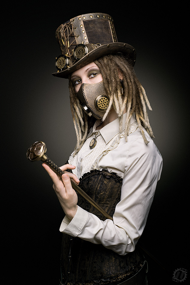 Photo Steampunk girl with cane in the top hat, goggle and mask
