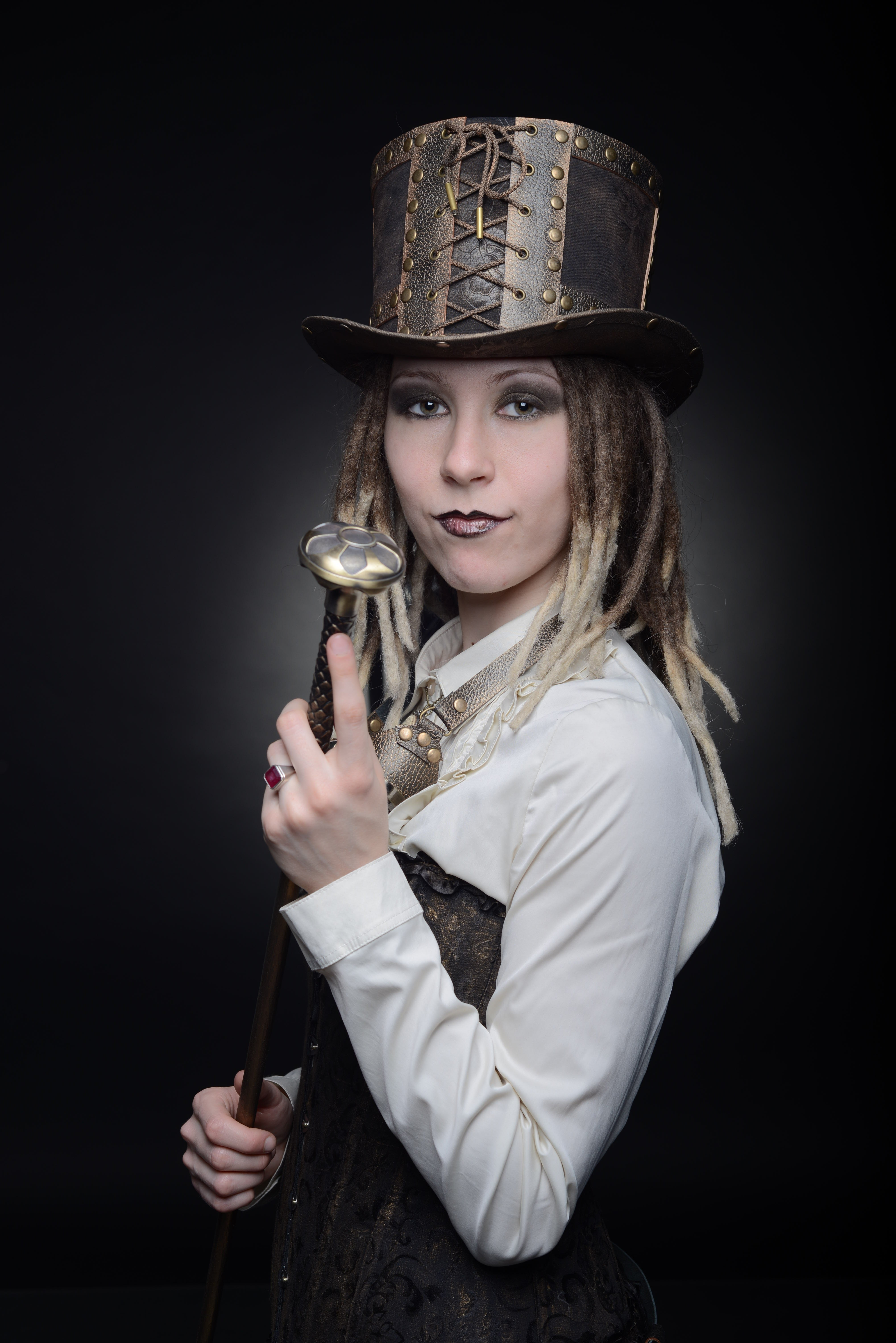 Фото девушки в стиле стимпанк в гогглых, цилиндре и с прогулочной тростью