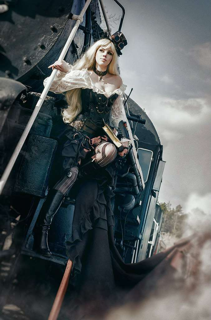 photo of the girl in steampunk style near locomotive